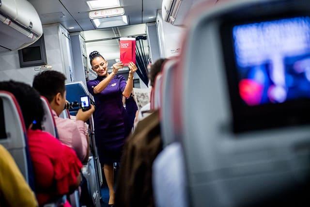 Flight Attendant demonstrating in front of passengers